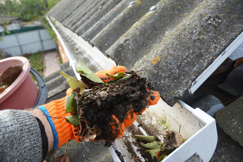 a gloved person removing dirt from the gutters